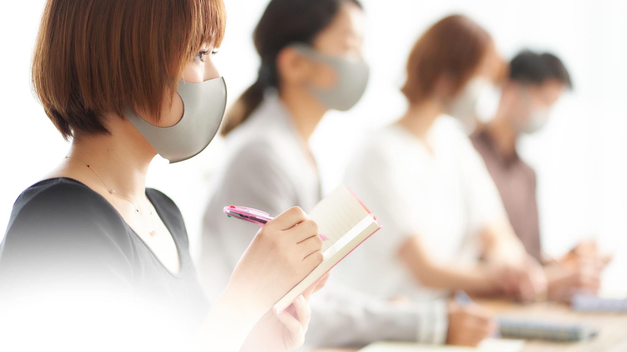 メモをとるマスク着用の受講生