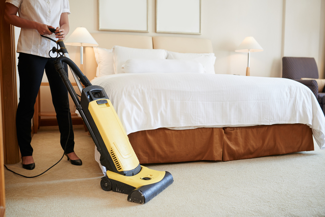 Cropped image of maid cleaning carpet in hotel room