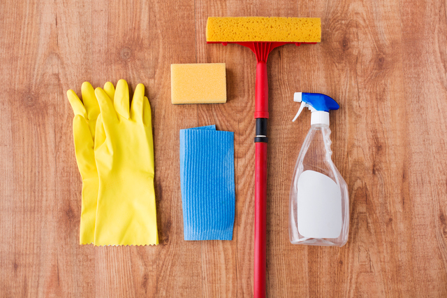 housework, housekeeping and household concept - swab with rubber gloves and cleaning stuff on wooden background