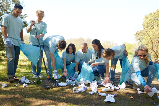 volunteering, charity, people and ecology concept - group of happy volunteers with garbage bags and rake cleaning area in park