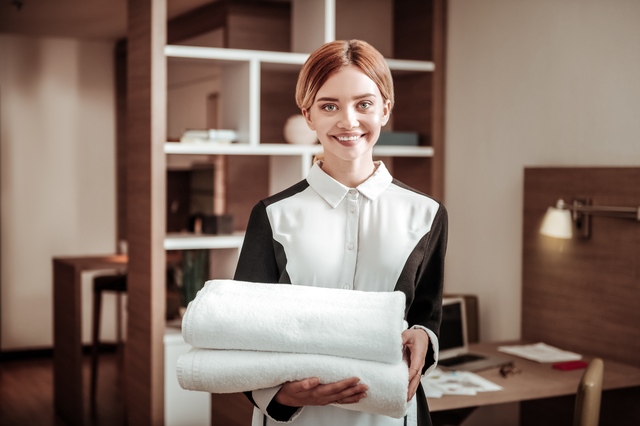 Pleasant maid. Young pleasant blonde-haired hotel maid holding white towels while working