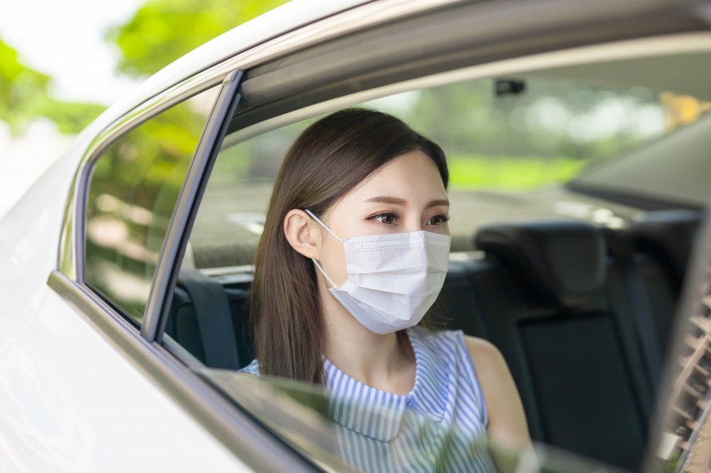 asian business woman commute by taxi and she wear face mask to avoid infectious diseases coronavirus